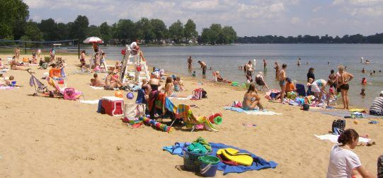 Beachgoers on the sand sitting on towels