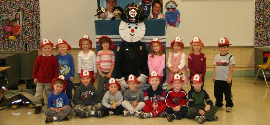 Fire Prevention Children's Class - children sitting and standing next to a mascot, with fire hats