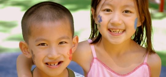 Two children smiling with face paint on their cheeks