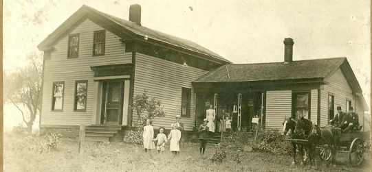 Family standing in front of home